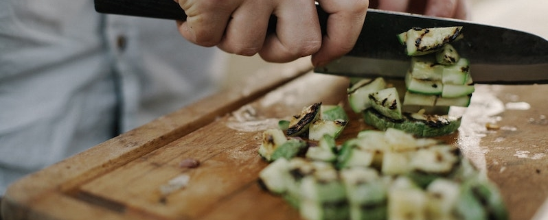 Chef chopping vegetables on wooden chopping board
