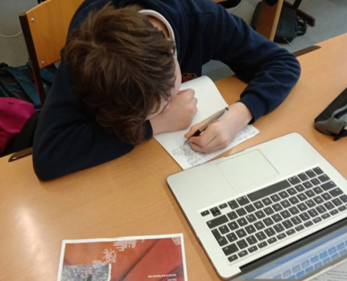 Student writing on a paper in a class room