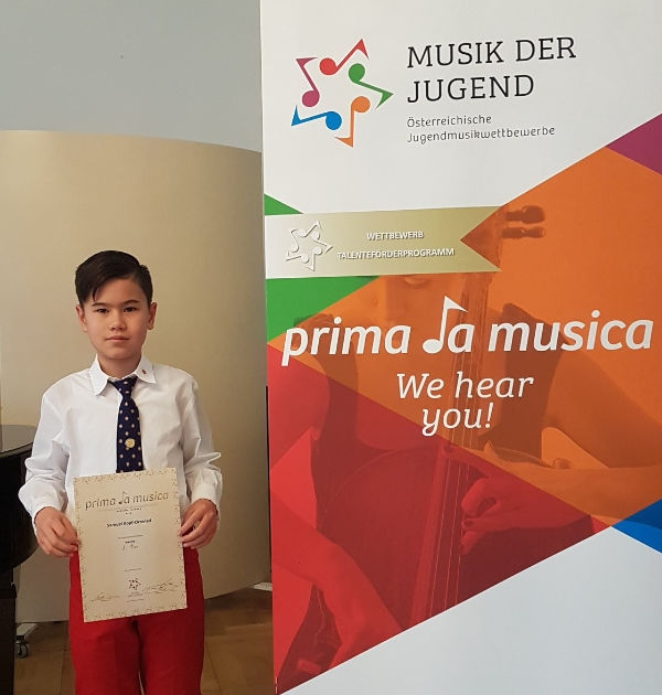 Boy with diploma at Prima La Musica Competition