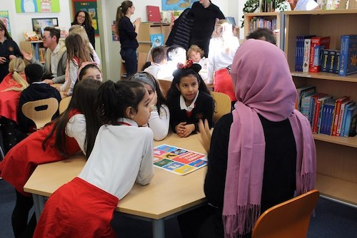 Woman telling a story to young students