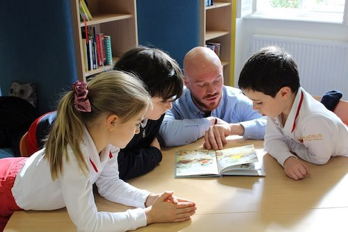 teacher reading a book for students at a table