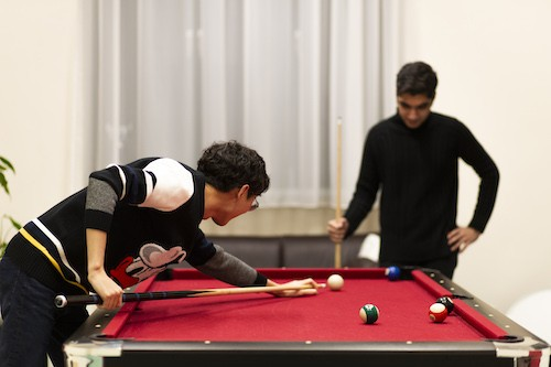 Two boys playing billiard