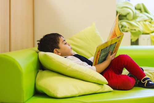 Child laying in green sofa while reading a book