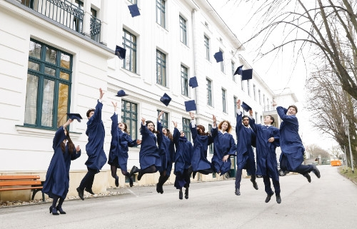 Graduates jumping and throwing their hats in the air
