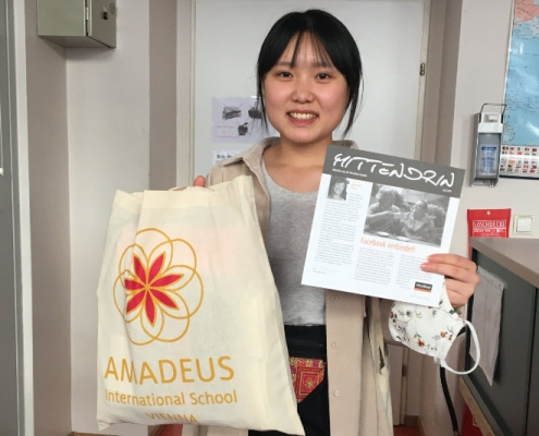 Girl holding a white AMADEUS bag and a flyer