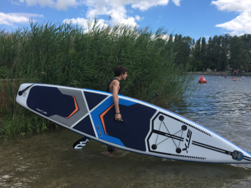 Boy carrying a stand up paddle board