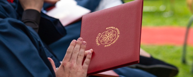Graduate holding certificate with school logo