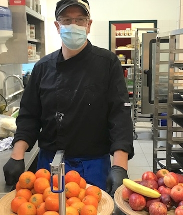 Chef standing in front of fruit while wearing a face mask