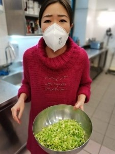 Lady with a white mask and a red sweater holding a bowl with green vegetables