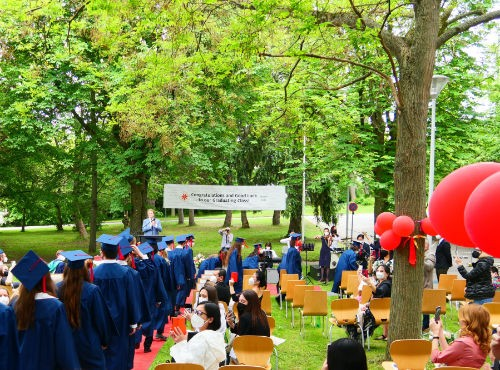 Graduates in blue gowns walking in row in green park