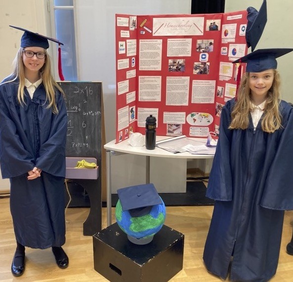 two young students presenting their project in blue graduation gown